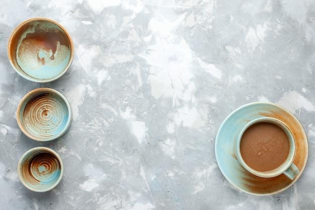 Vista dall'alto di piatti vuoti con caffè al latte sulla scrivania leggera, bere caffè al latte delizioso