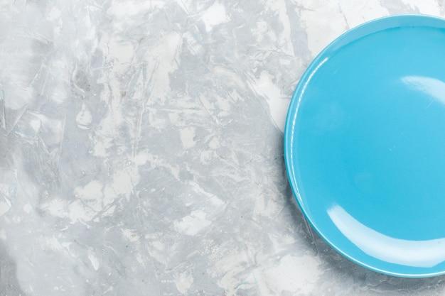 Vista dall'alto piatto rotondo vuoto blu ed su scrivania bianca