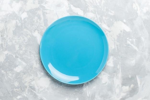 Vista dall'alto piatto rotondo vuoto blu ed su superficie bianca