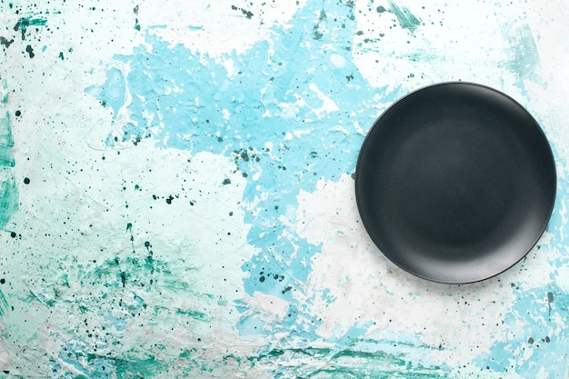 Top view empty round plate dark colored on the light blue background color plate kitchen cutlery glass