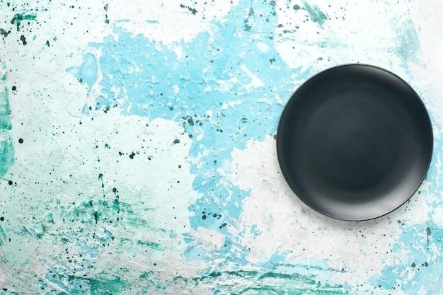 Вид сверху пустая круглая тарелка темного цвета на голубом фоне цветная тарелка кухонные столовые приборы стакан