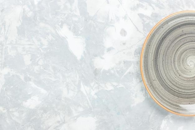 Вид сверху пустая круглая тарелка серого цвета на белом столе