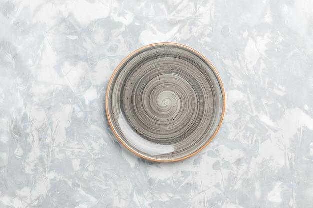 Вид сверху пустая круглая тарелка серого цвета на белой поверхности