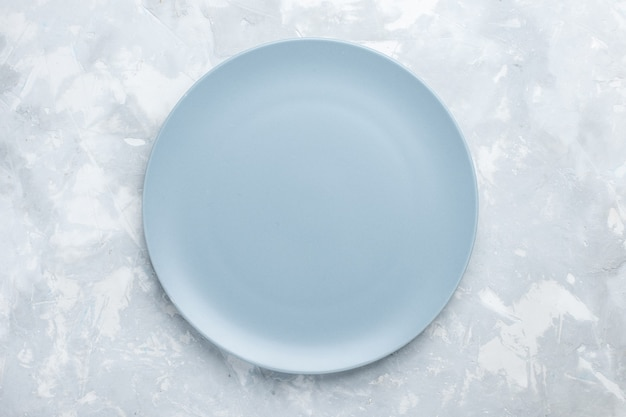 Top view empty round plate ice-blue colored on the white desk plate cutlery kitchen food