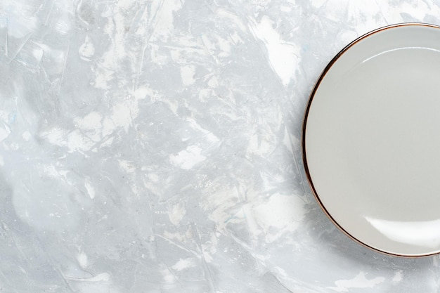 Вид сверху пустая круглая тарелка на белой поверхности