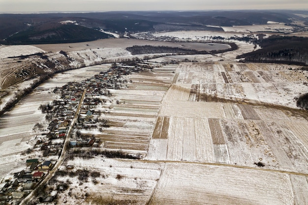 Top view of empty snowy fields, houses along road and woody hills on blue sky . aerial drone photography, winter landscape.