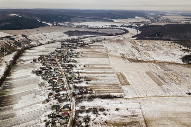 Top view of empty snowy fields, houses along road and woody hills on blue sky background. aerial drone photography, winter landscape.