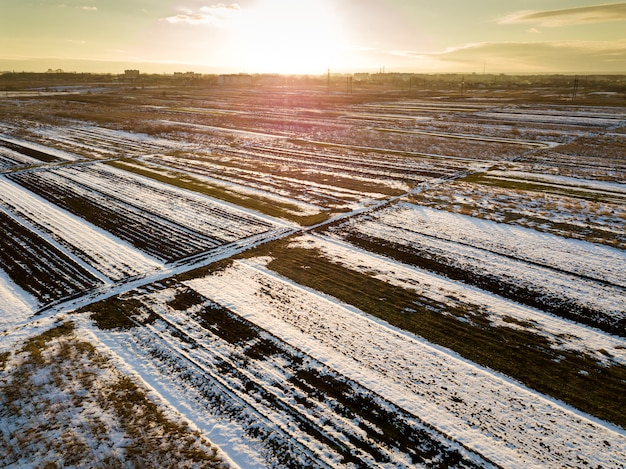 Top view of empty snowy fields patched landscape, dark horizon and bright sky on sunny winter day. aerial drone photography concept.