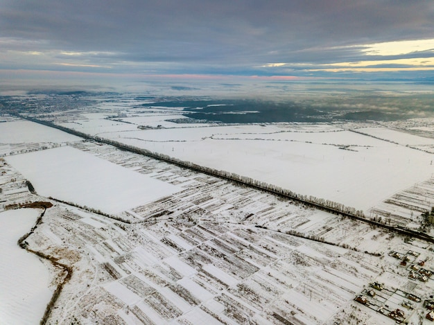 Top view of empty snowy fields on winter morning on dramatic cloudy sky. aerial drone photography concept.