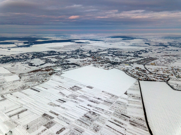 Top view of empty snowy fields on winter morning on dramatic cloudy sky background. aerial drone photography concept.