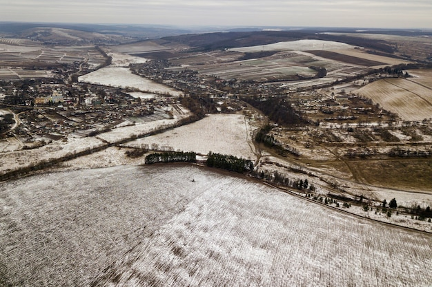 Top view of empty snowy fields and woody hills on cloudy sky. aerial drone photography, winter landscape.