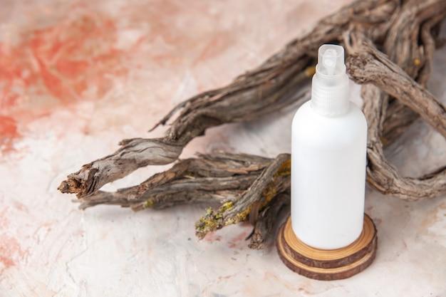 Vista dall'alto flacone spray vuoto sul ramo di un albero di tavola di legno su sfondo nudo
