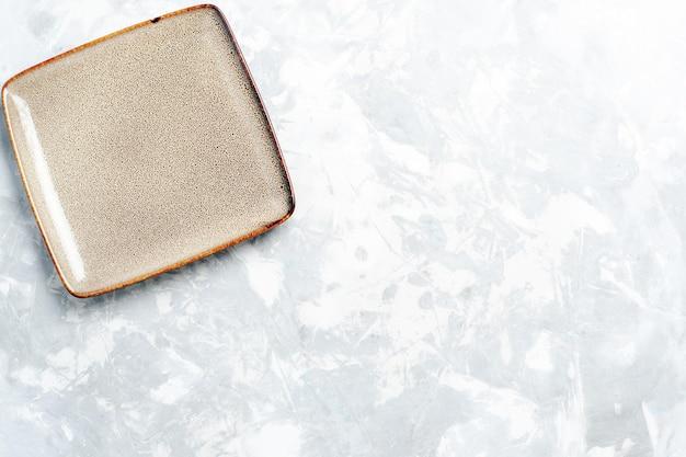 Vista dall'alto piatto quadrato vuoto marrone ed su scrivania bianca chiara
