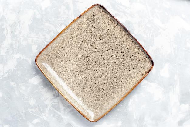 Vista dall'alto piatto quadrato vuoto marrone ed su superficie bianca chiara