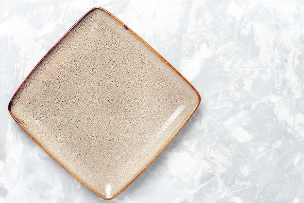 Вид сверху пустая квадратная тарелка коричневого цвета на белом столе