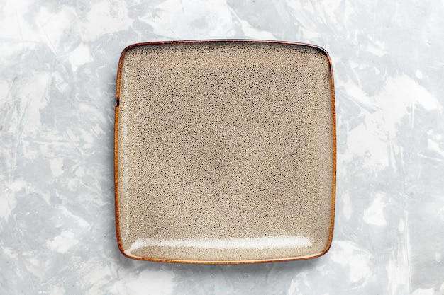 白い机の上に茶色の上面図空の正方形のプレート
