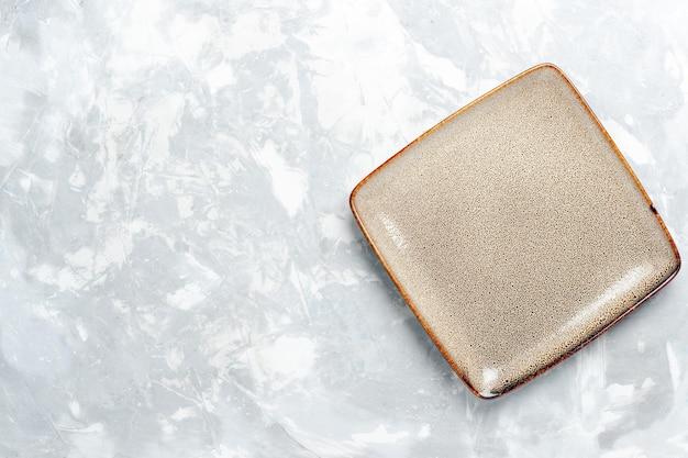 Вид сверху пустая квадратная тарелка коричневого цвета на белой поверхности