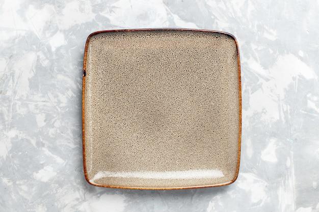 Vista dall'alto piatto quadrato vuoto marrone ed su scrivania bianca