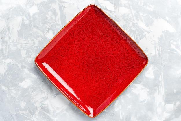 Vista dall'alto piatto quadrato vuoto rosso su superficie bianca