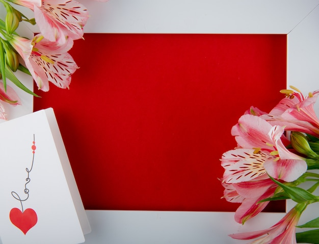 Top view of an empty white picture frame with pink color alstroemeria flowers and a postcard on red background with copy space