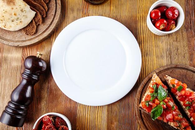 食事の平面図の空の白いプレート。天日干しトマト、ブルスケッタ、木製の背景上の調理器具の構成で食品を提供するための空白のプレート。フラットレイ