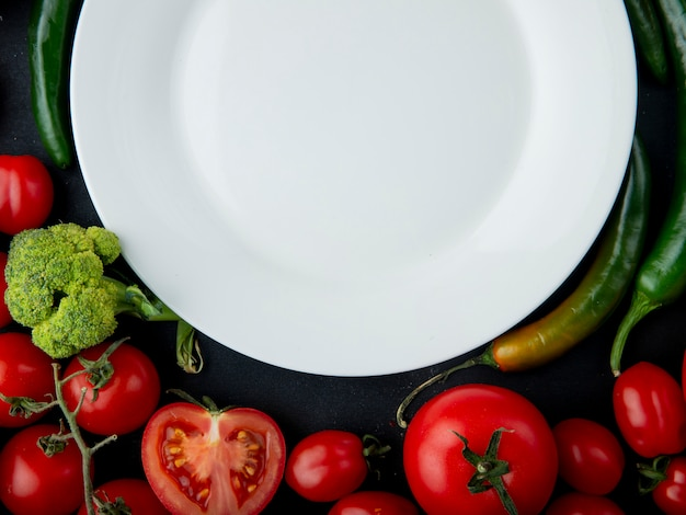 Top view of an empty white plate and fresh vegetables laying around ripe tomatoes and green chili peppers on black background