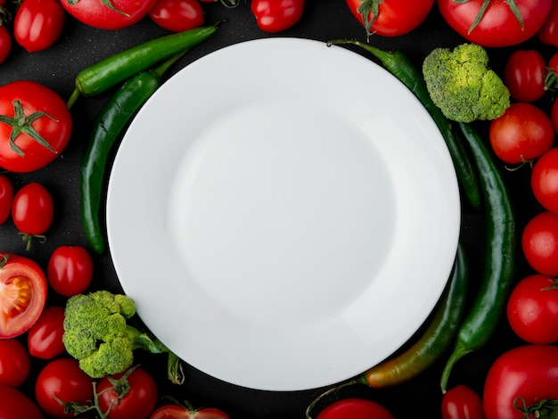 Top view of empty white plate and fresh vegetables laying around tomatoes broccoli green chili peppers on black background