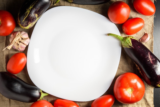 Top view of empty white plate in the middle and vegetables around. copy space.