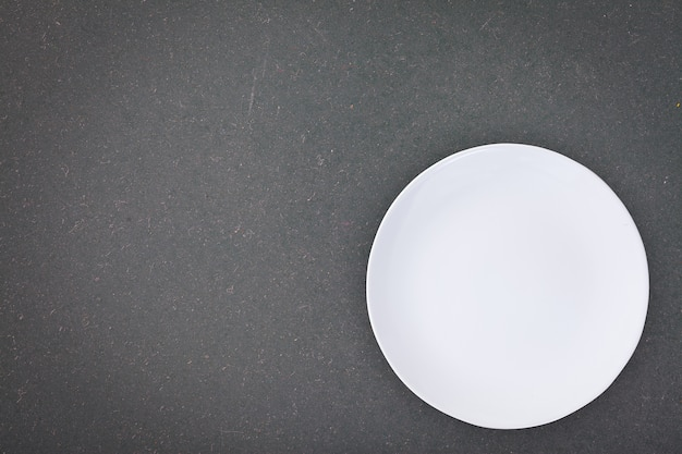 Top view of an empty white plate placed on a blackboard with copy space.