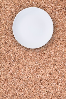 Top view of an empty white plate placed on cork background with copy space.