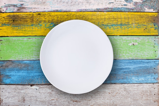 Top view of empty white plate put on colorful wood table with space for copy.