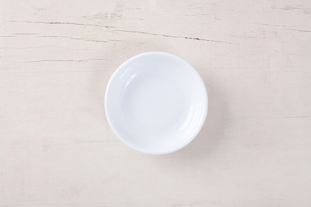 Top view of empty white plate put on white wood table with space for copy.