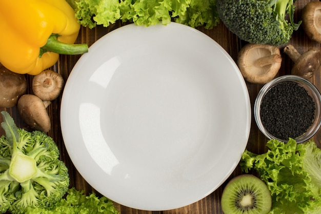 Top view of empty white plate and vegetables