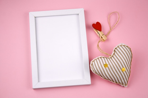 Top view empty white wooden frame  and fabric soft toy in a shape of heart pastel pink background