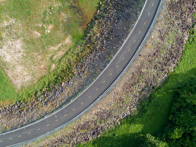 Top view an empty winding tarmac road with green trees and grass om roadside from drone aerial view from above.