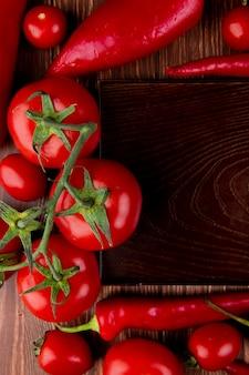 Vista superiore di un vassoio di legno vuoto e dei pomodori ciliegia rossi dei peperoncini degli ortaggi freschi e dei peperoni dolci rossi su rustico