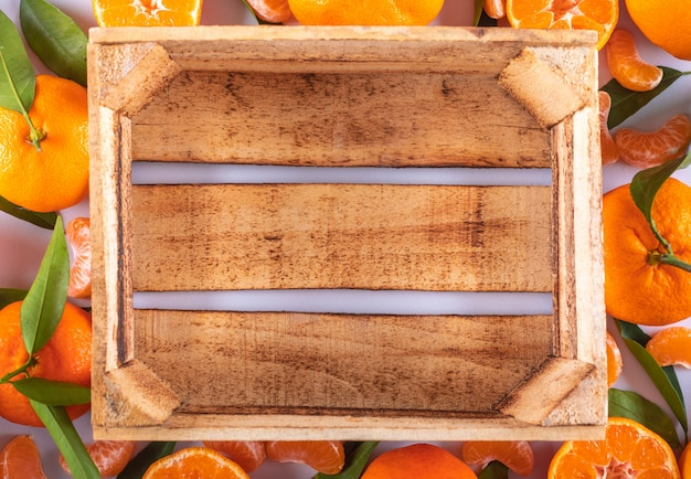 Top view empty wooden box surrounded with mandarins