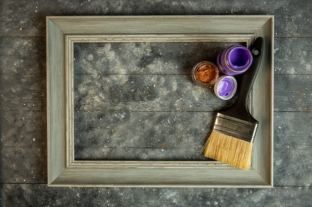 Top view of empty wooden picture frame with acrilic paints and paint brush