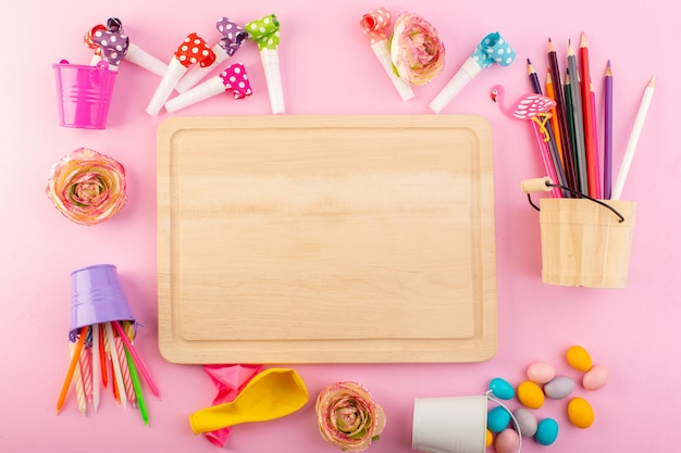 A top view empty wooden table with pencils candies flowers on the pink table celebration decoration color