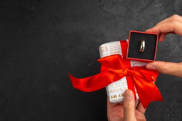 복사 장소와 어두운 배경에 손에 상자 선물의 상위 뷰 약혼 반지