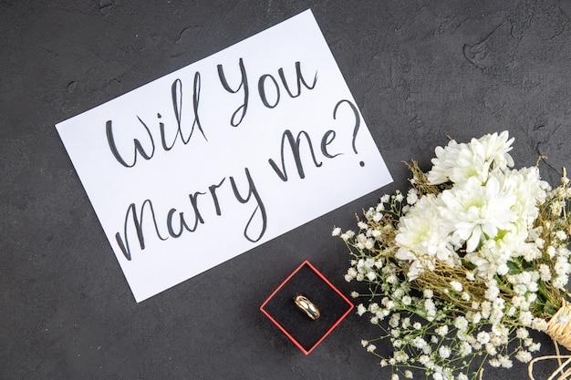 Вид сверху обручальное кольцо в красной коробке, выйдешь за меня замуж написано на бумажных цветах на столе