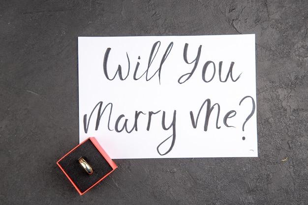 Вид сверху обручальное кольцо в красной коробке, выйдешь за меня замуж написано на бумаге на темном фоне