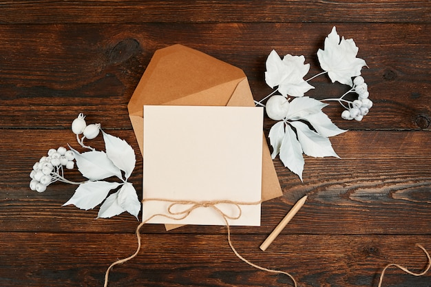 Top view of envelope and blank kraft greeting card with white leaves a