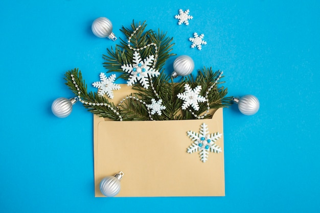 Top view of envelope with christmas composition on the blue  background. copy space.