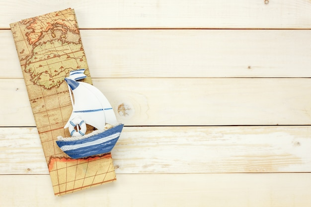 Top view essential travel items.the boat map  on white  wooden background with copy space.
