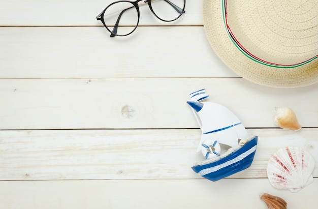 Top view essential travel summer items.the boat eyeglasses  hat shell on white  wooden background.