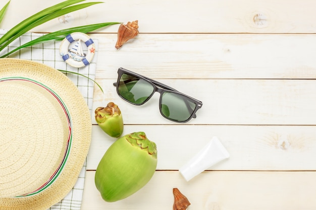 Top view essential travel summer items.the sunblock  coconut hat  sunglasses on white  wooden background.