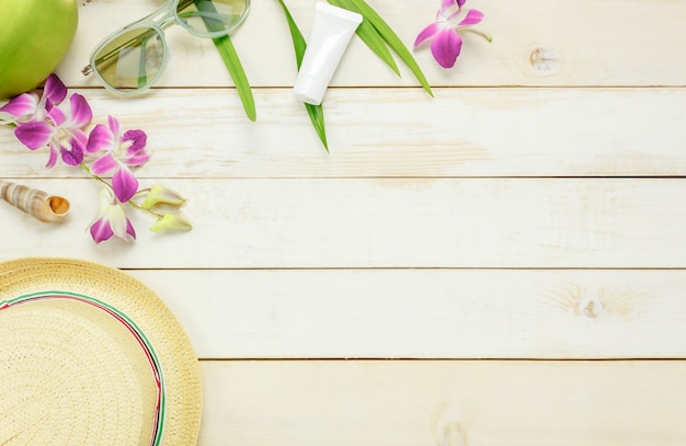 Top view essential travel summer items.the sunblock moisturizing  hat  sunglasses orchid on white  wooden background.