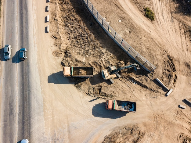 Top view of excavator machine dig soil and put it into industrial dumper truck