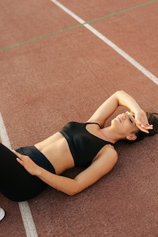 Top view of exhausted woman in sportswear resting on track after finish in challenging race
